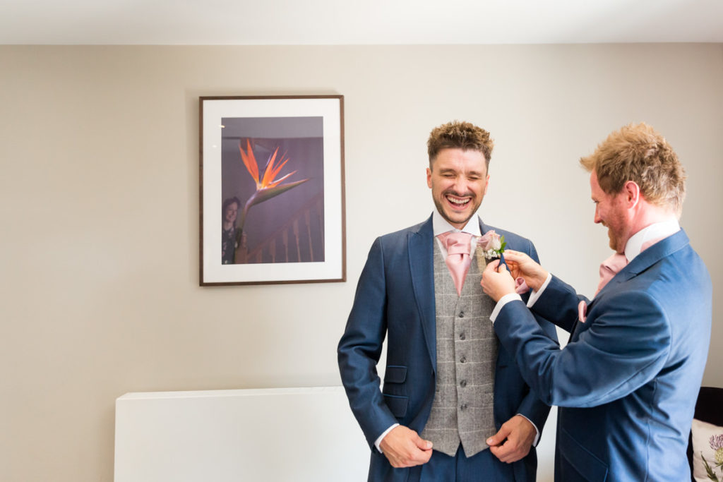 Groom having tie tied