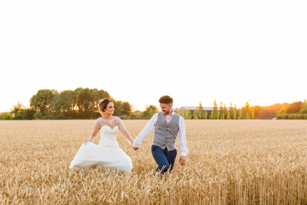 Bride and groom walking through corn field