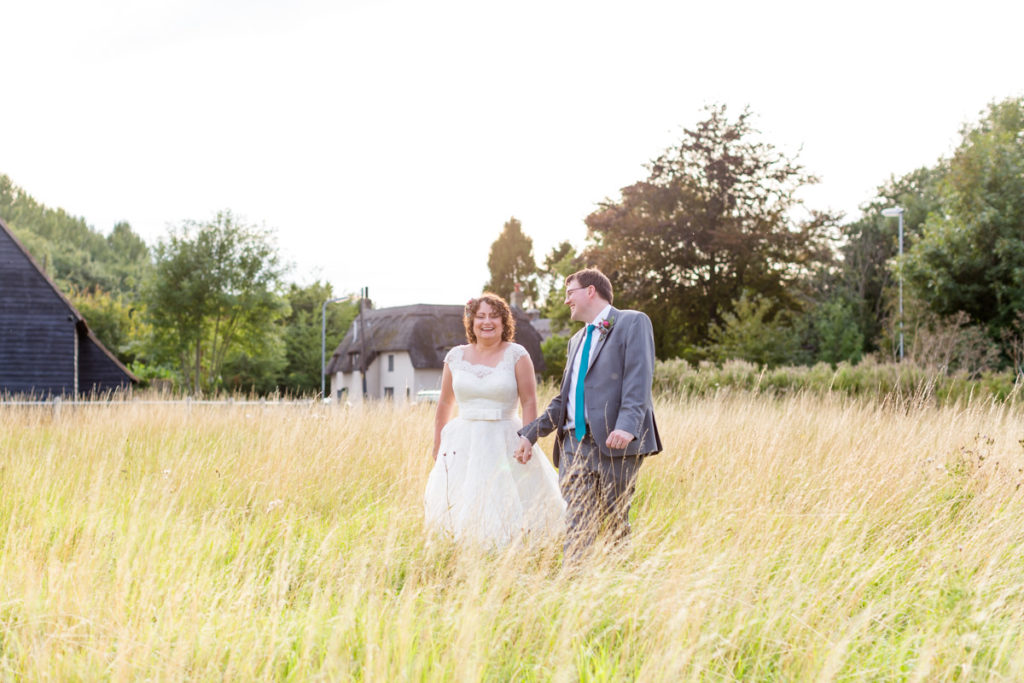 Bride and groom in a field of long grass