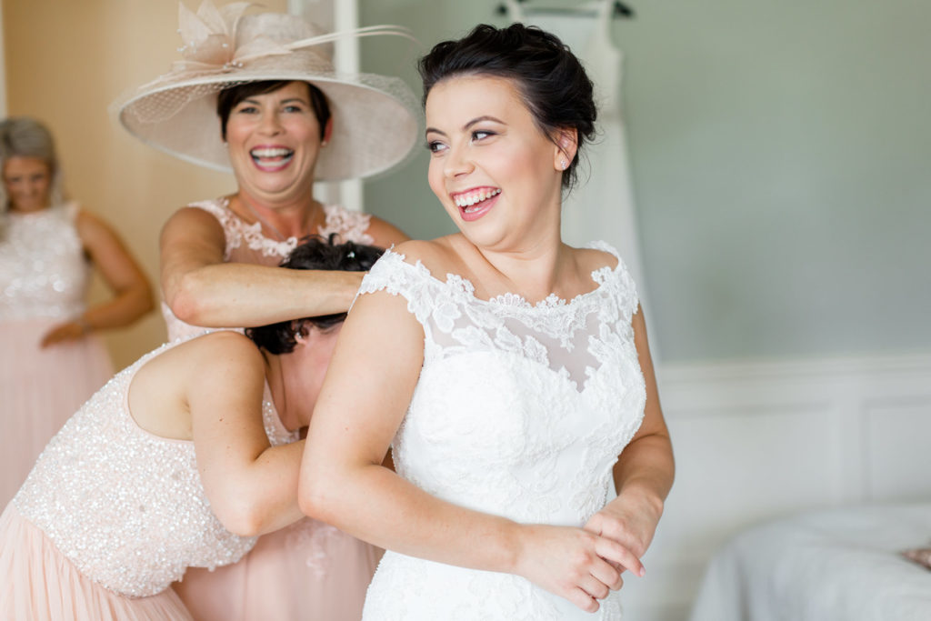 Mother of the bride helping her daughter into her wedding dress