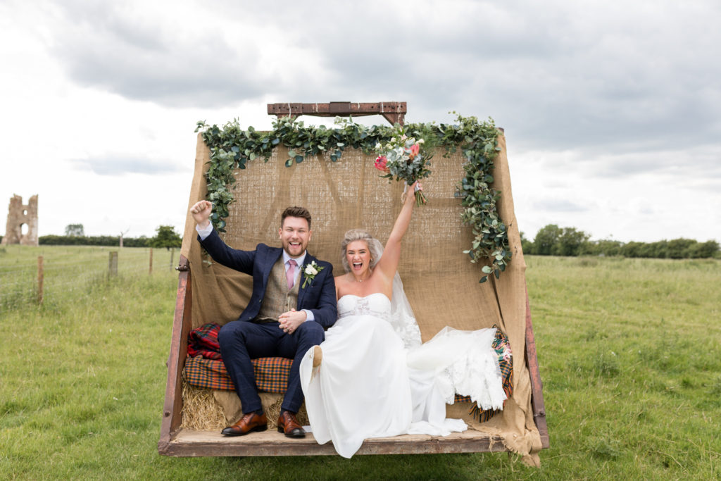 Bride and groom on tractor at Godwick Barn Norfolk