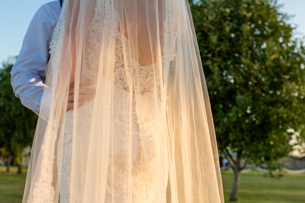 Details of bride's dress and veil in sunlight