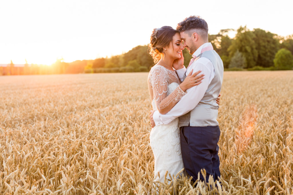 Bride and groom in a corn field at sunset
