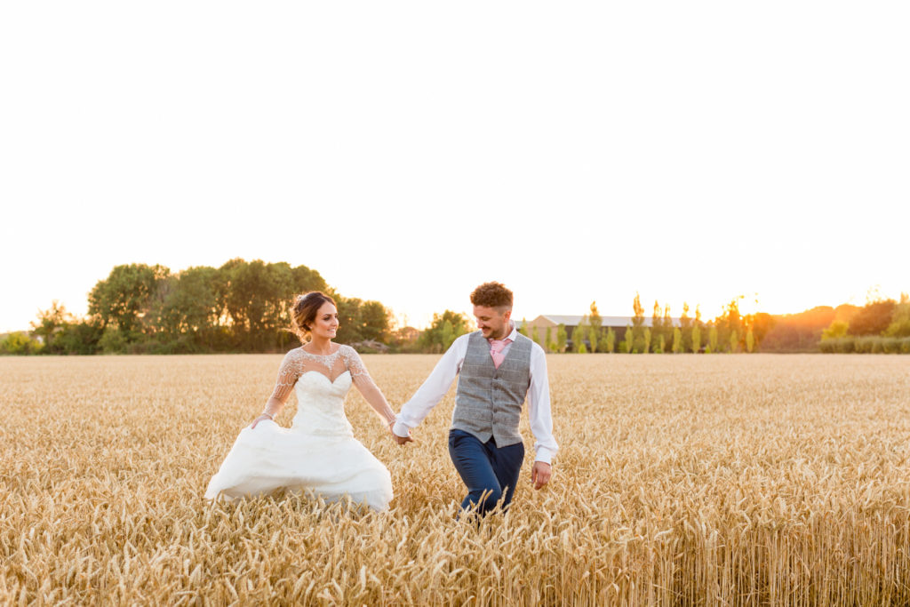 Bride and groom at Bassmead Manor barns in cornfield