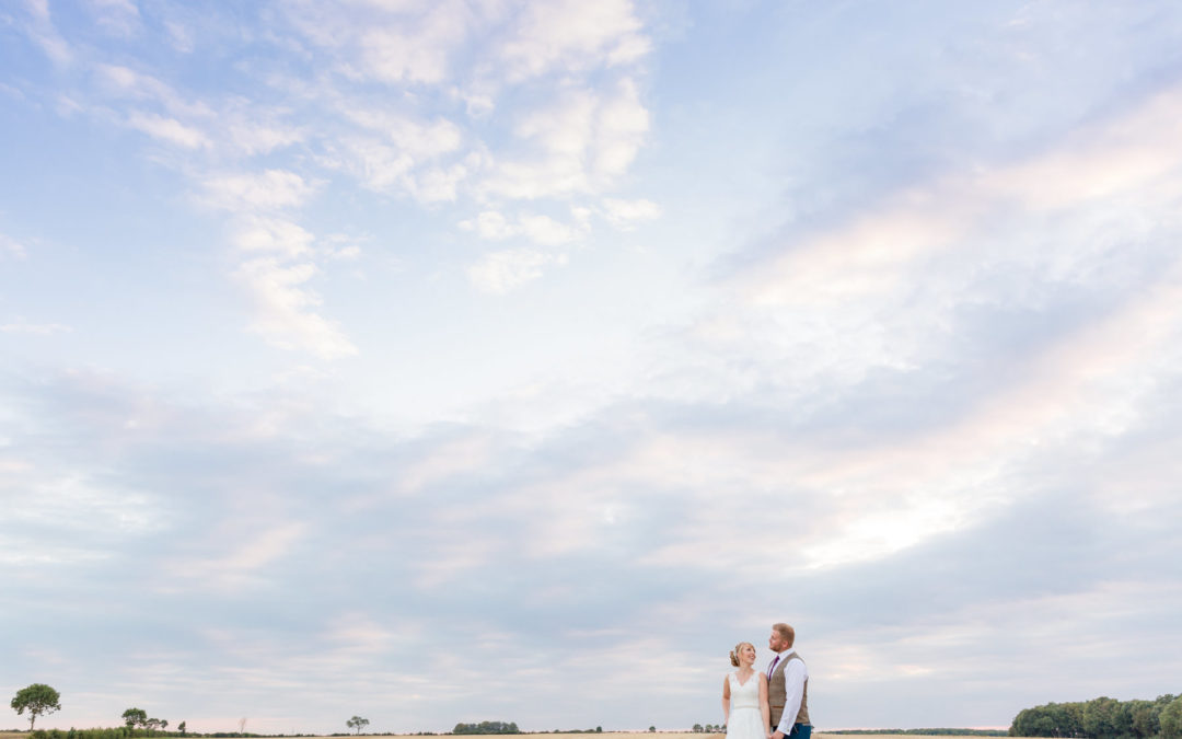 Bride and groom against massive sky at Childerley Barn