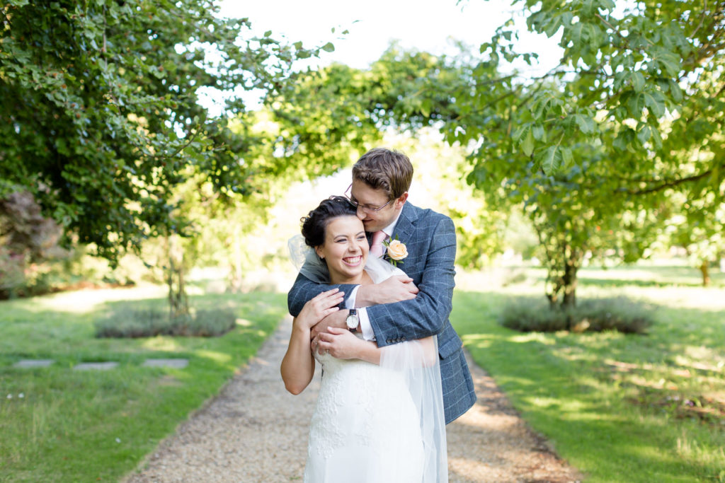 Bride and groom cuddling at Chippenham Park Ely