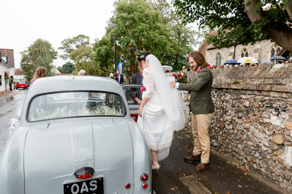 Groom holding bride's dress as she gets into car