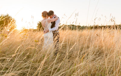 Bride and groom snuggling in grass field