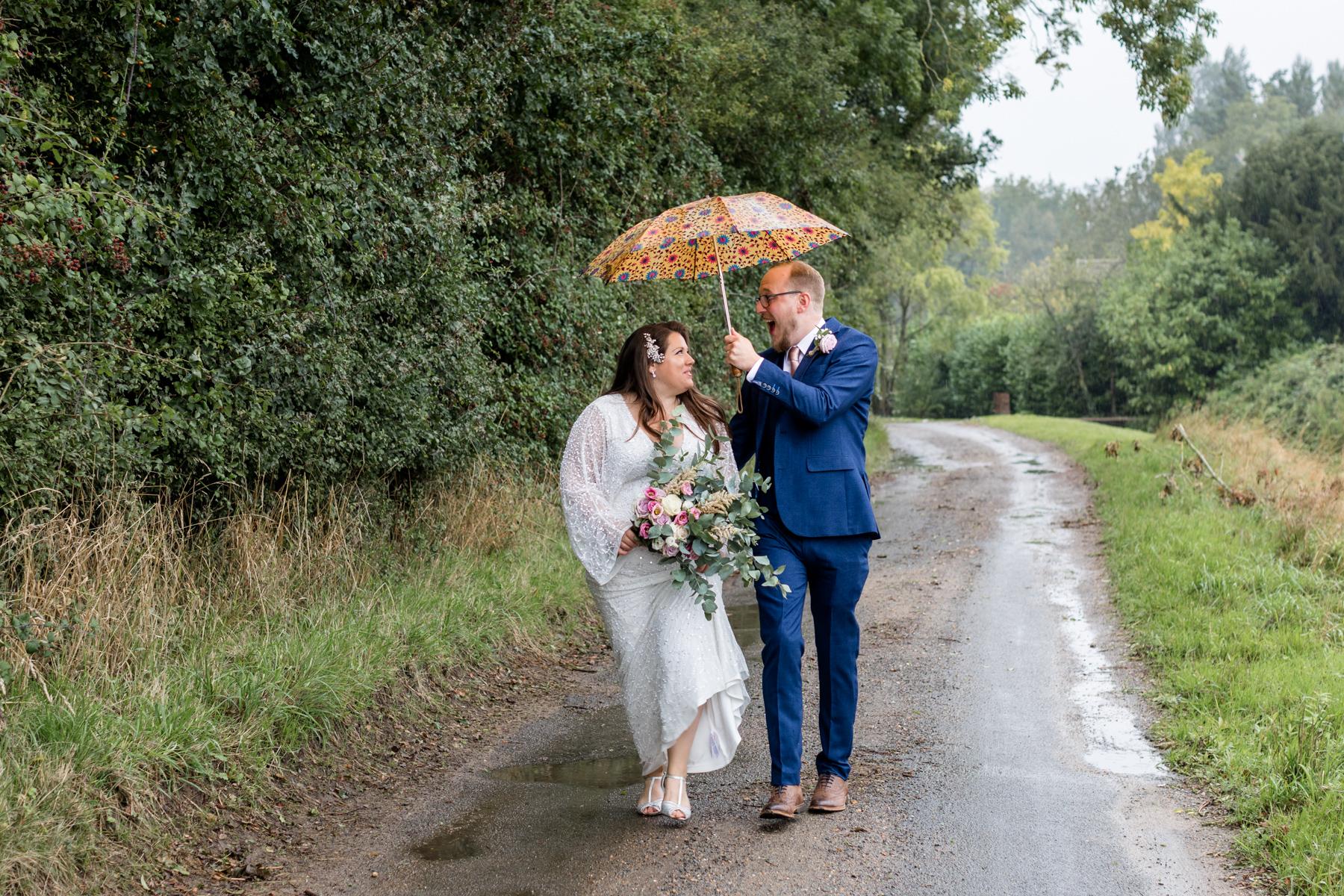 Nriade and groom walking in the rain