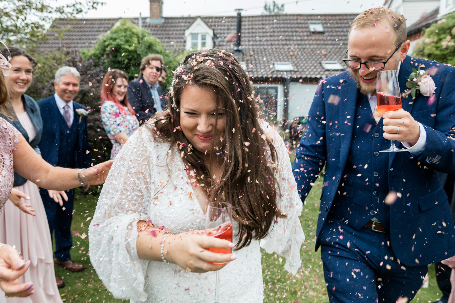 Confetti tunnel in the rain at Norfolk wedding