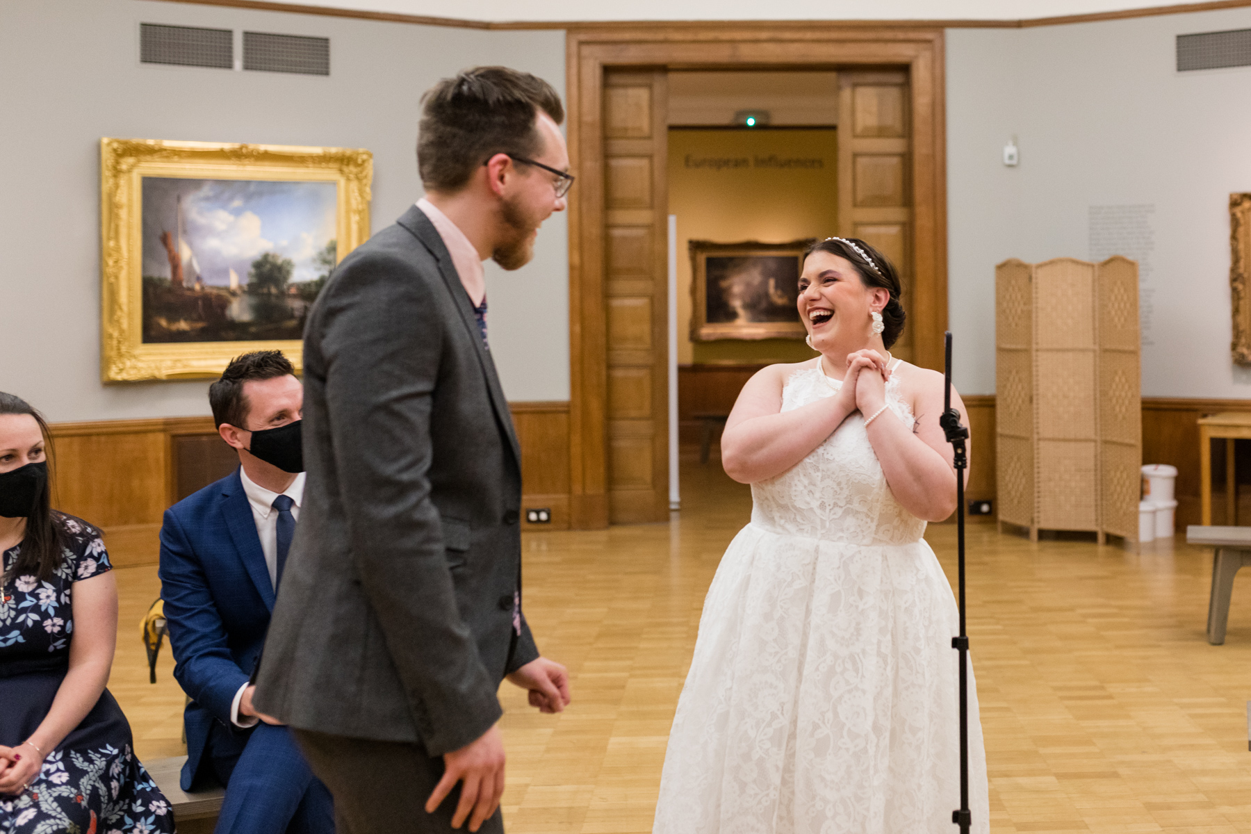 Bride and groom laughing with guests via video link