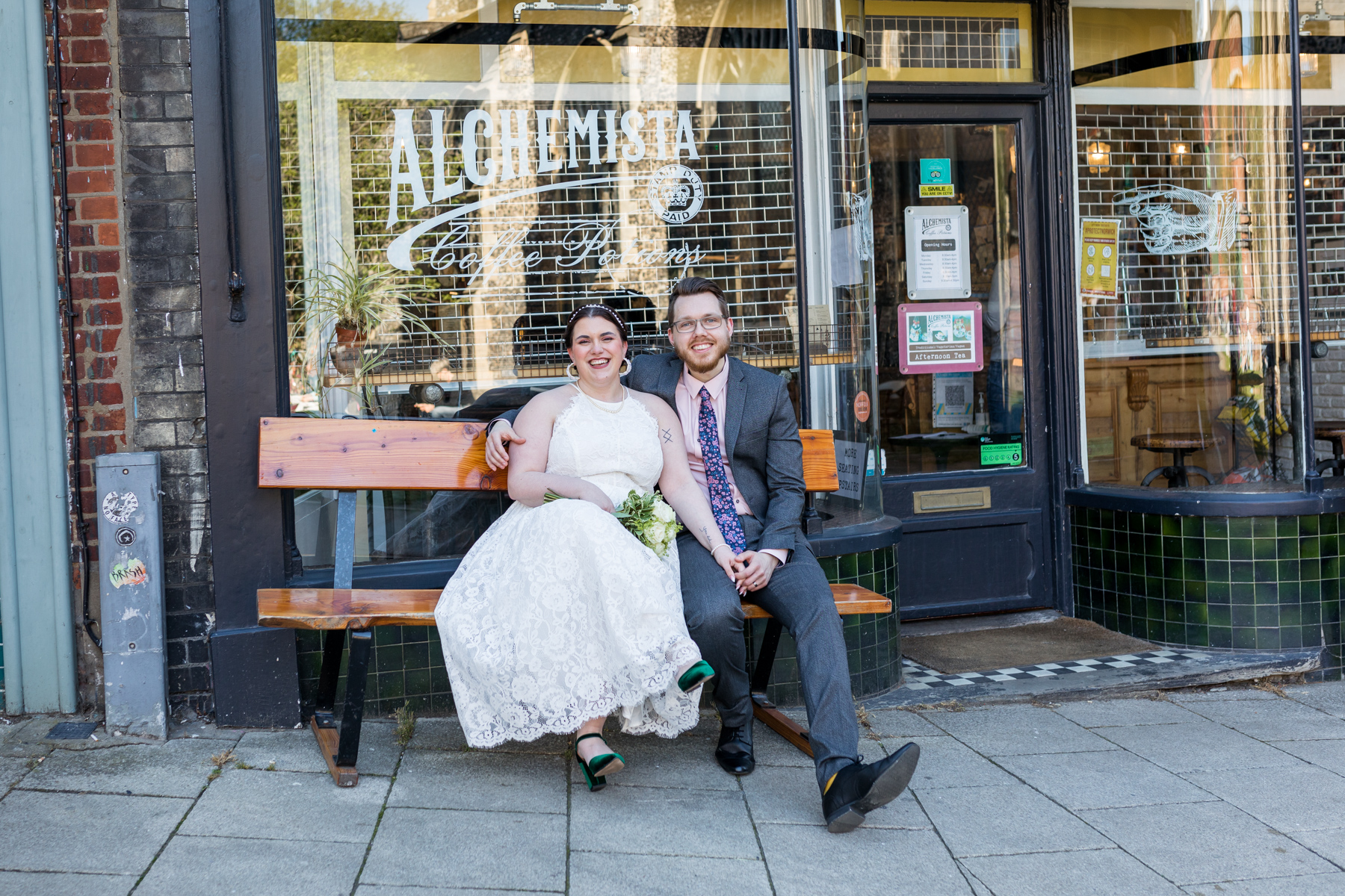 Bride and groom sitting outside cafe